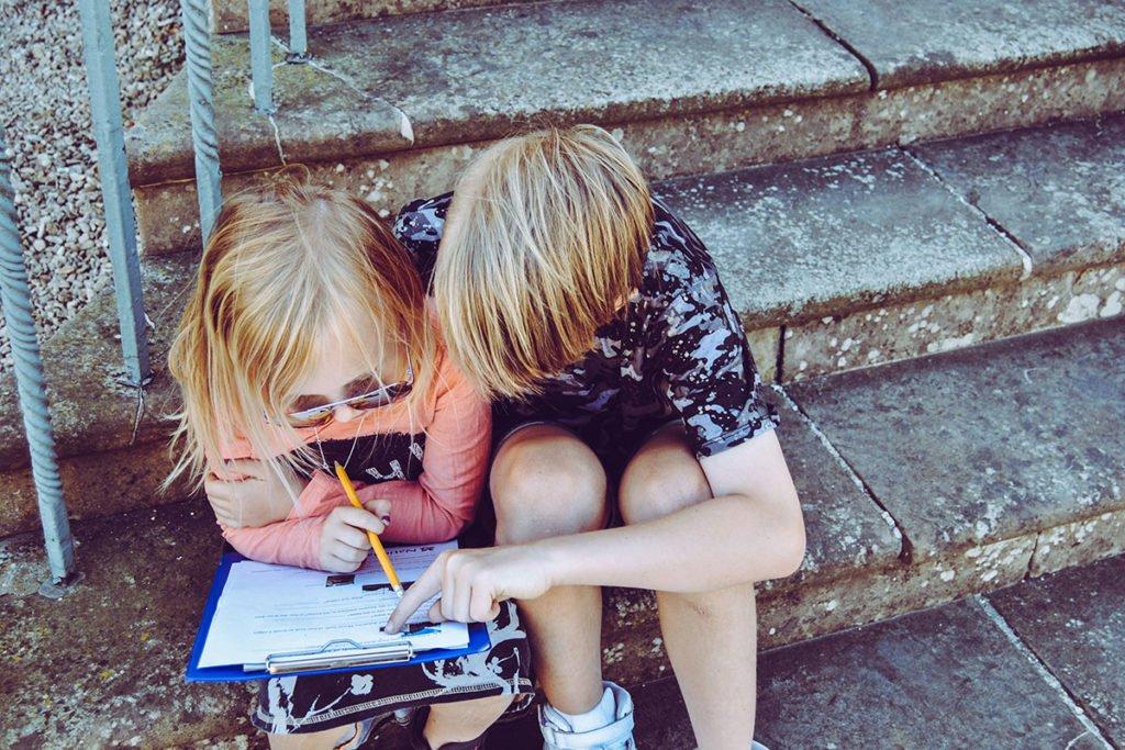 Lapsi auttaa toista kotitehtävissä