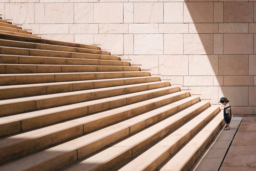 Pieni lapsi seisoo suurten portaiden alapäässä