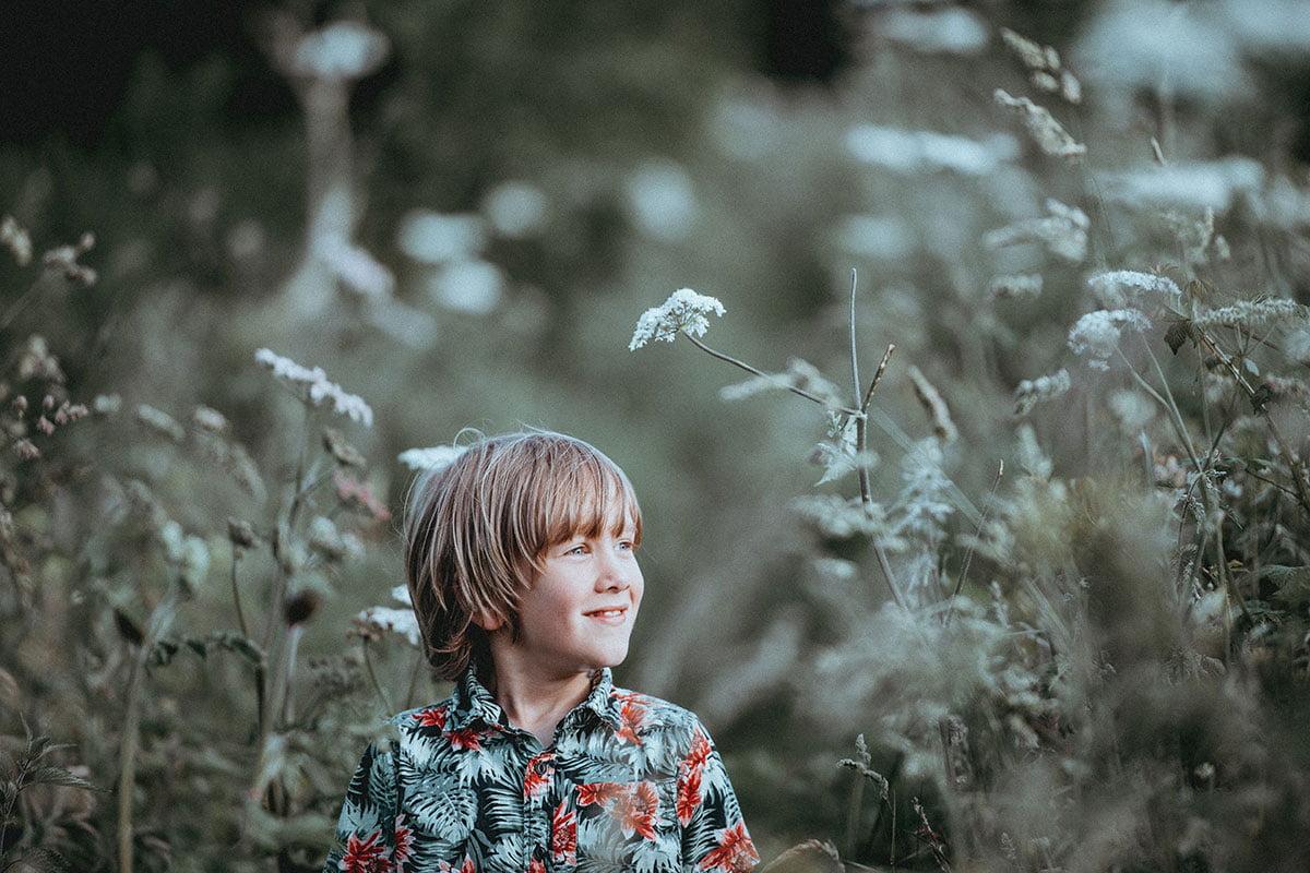 Hymyilevä poika seisoo pellolla.