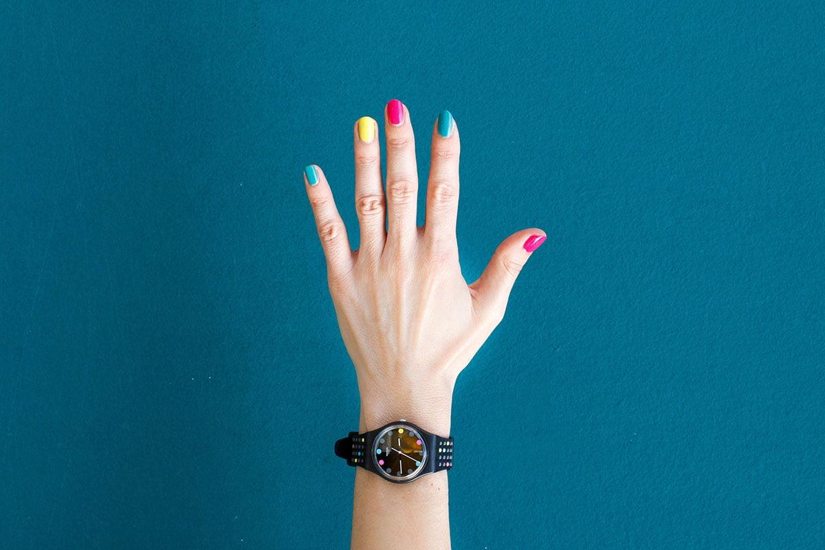 Käsi, jossa on viidelä värillä lakatut kynnet