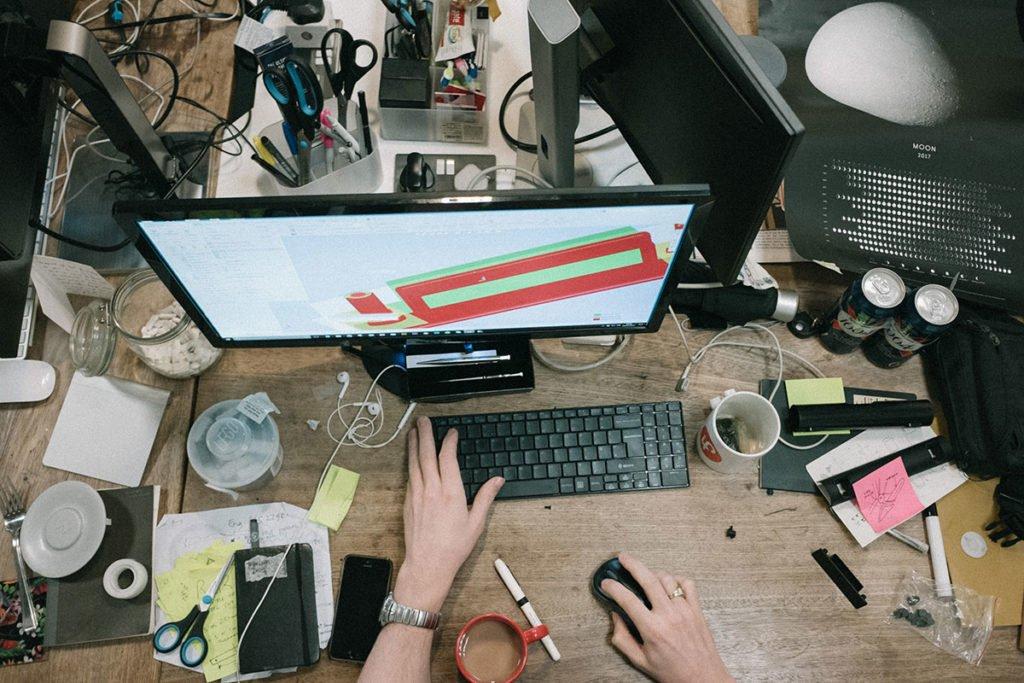 Tietokoneen näyttö ja muita tavaroita työpöydällä