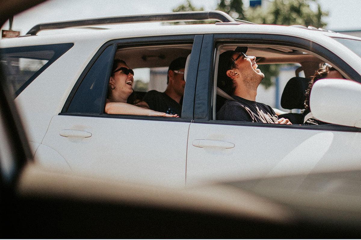 Ystävykset nauravat autossa.