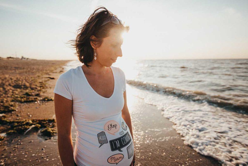 Raskaana oleva nainen rannalla